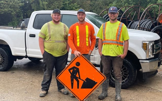 Three crew members holding a Men-at-Work sign